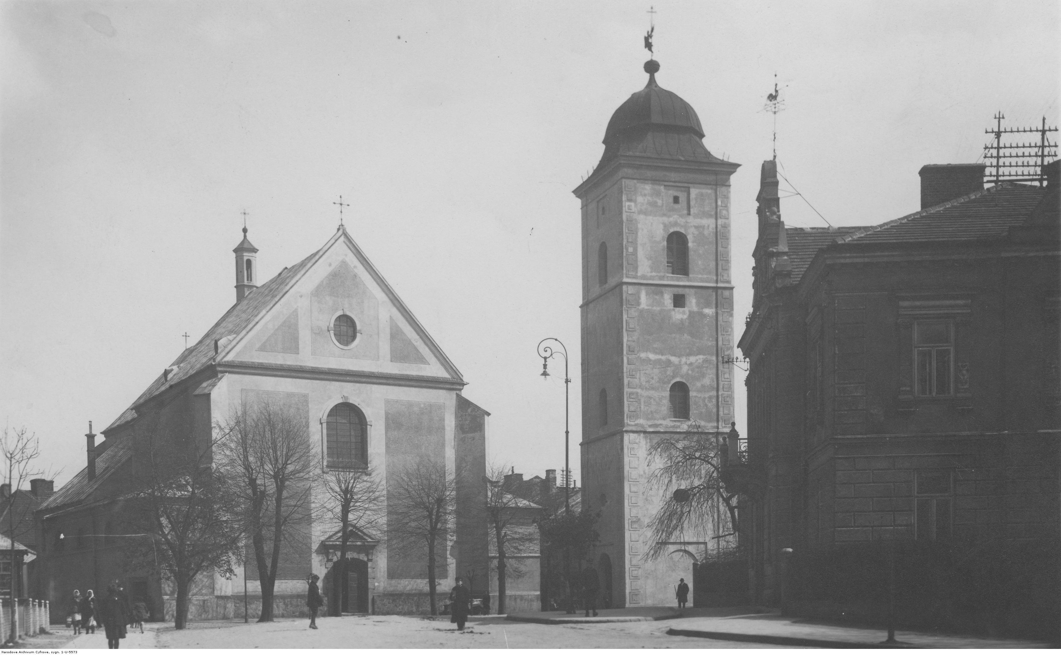 Kościół Farny świętych Wojciecha i Stanisława. Widok zewnętrzny kościoła wraz z najstarszą budowlą miasta dzwonnicą, rok 1918-1939